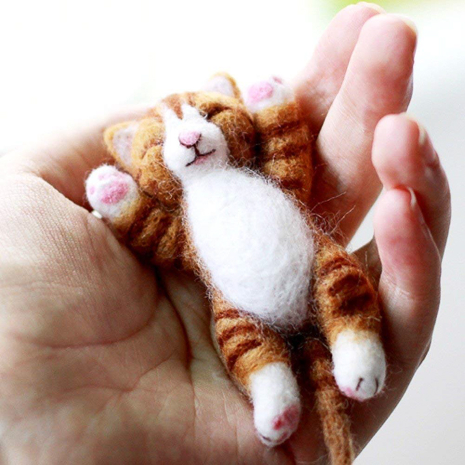 The sweetest little lazy tabby cat felted animal in the palm of a woman's hand.