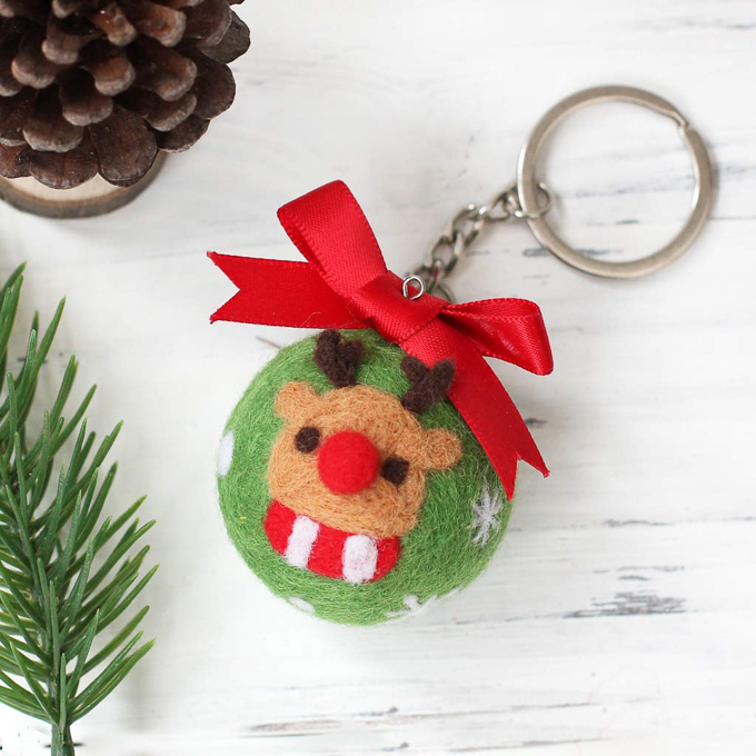 A Christmas ornament made with green felt and a small reindeer applique on the front