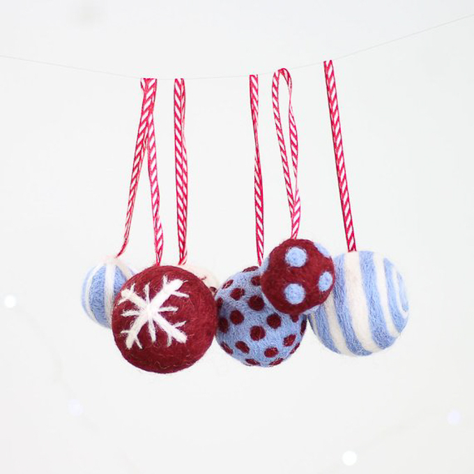 Light blue, burgundy and white round felted ornaments hanging on red and white ribbon.