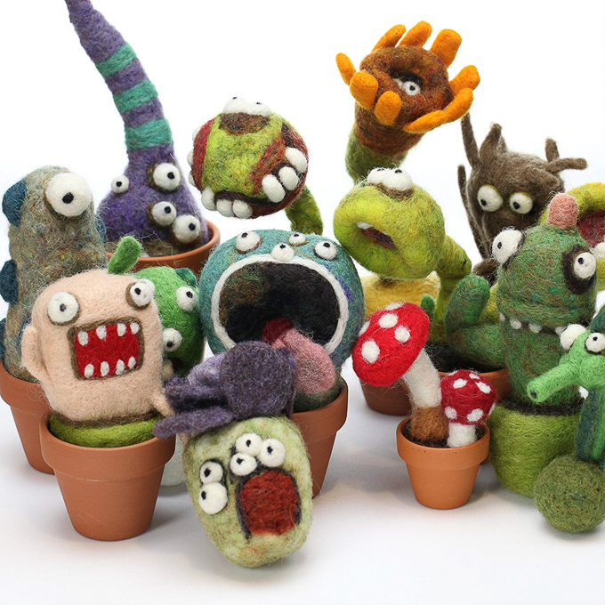 The cutest, craziest collection of needle felted monster cacti in small terra cotta pots.
