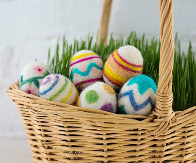 A half dozen beautiful, multi-colored Easter eggs from felted wool arranged in a wicker basket with green grass