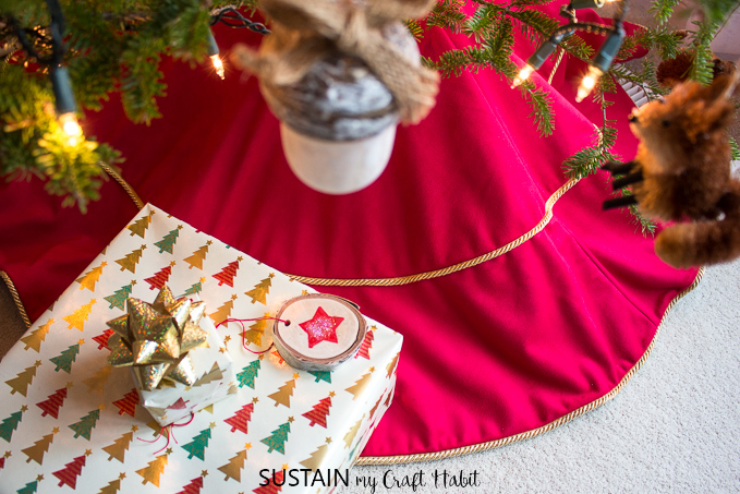 View from above of a red and gold Christmas tree skirt, under a tree with Christmas gifts