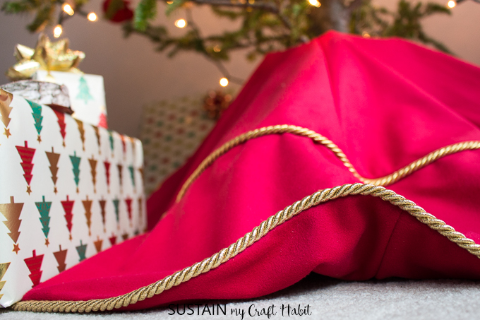 Close up view of gold piping on the edge of a tree skirt made with red velour