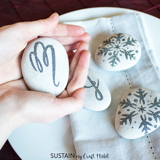 SO PRETTY! Create elegant monogrammed napkin weights with beach stones and some glitter vinyl. Perfect for a Christmas, New Year's Eve, wedding or bridal shower table setting. #cricutmaker #cricutcrafts #weddingtable #tablesetting #tablescape #newyearseveparty #rockcrafts #monogram #diy #napkinweights