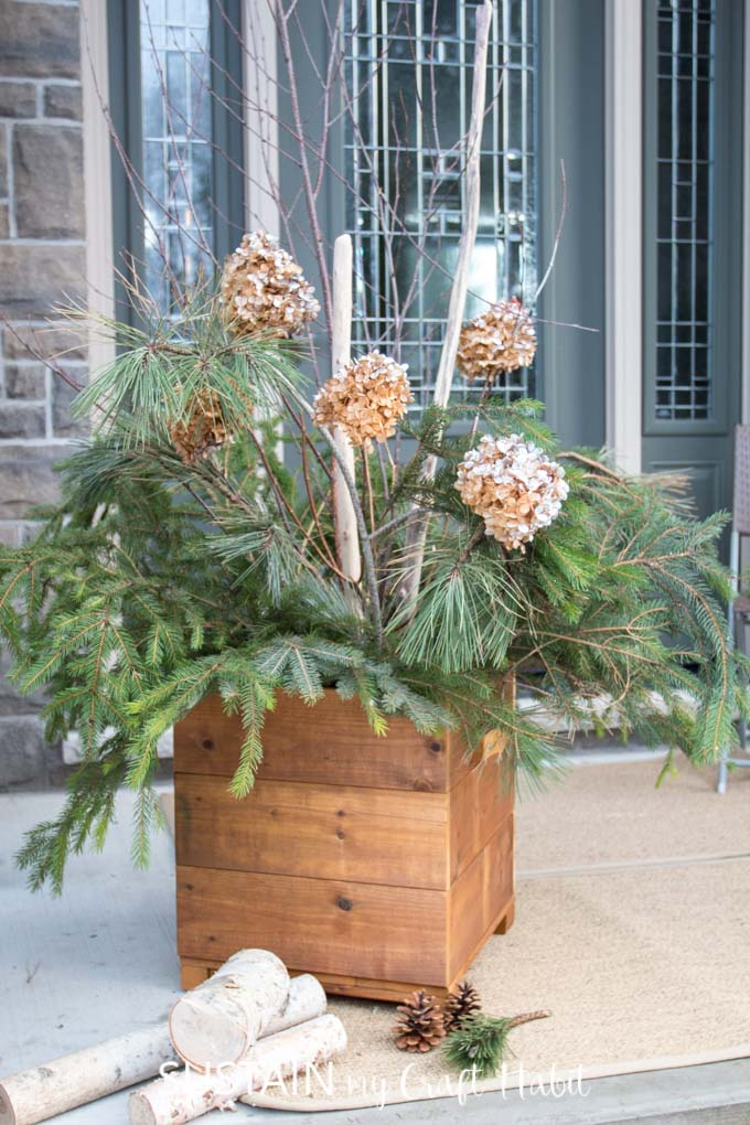 A cedar DIY planter box filled with pine greenery and branches on a front porch