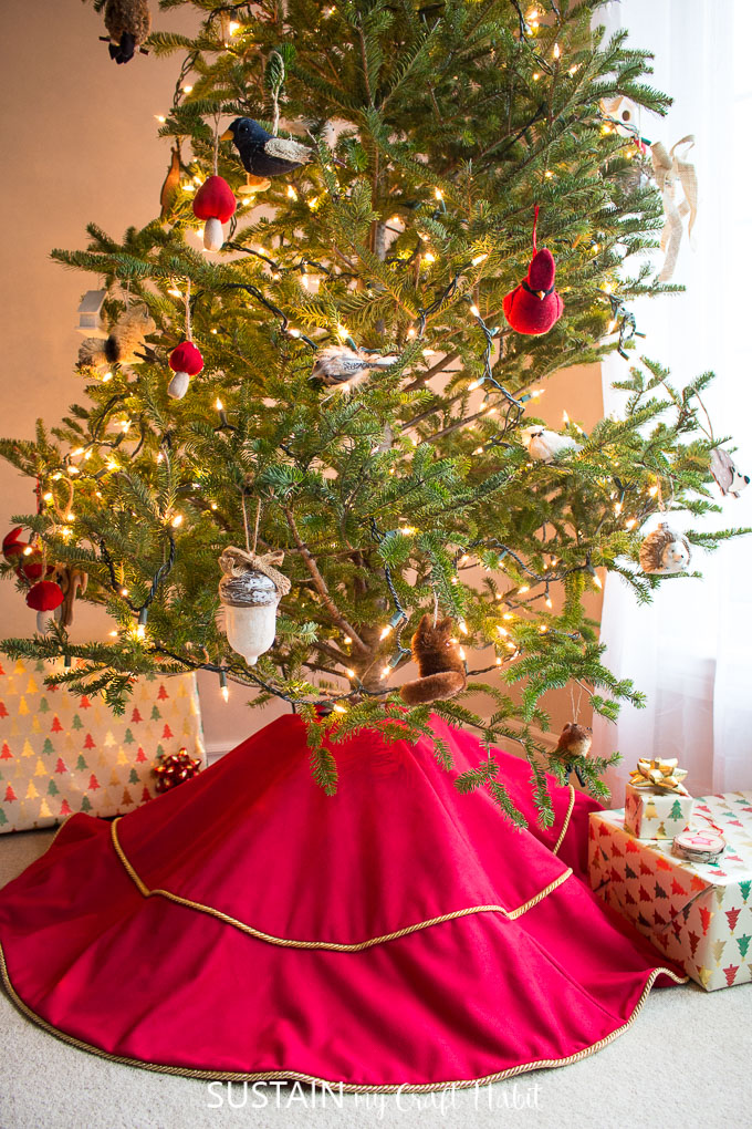 A red velour tree skirt with gold edging underneath a natural Christmas tree