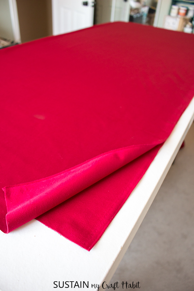 A large piece of red velour on a table being prepared to make a tree skirt for Christmas