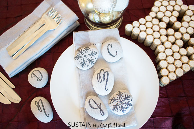 A festive table setting displaying monogrammed and embellished stones using a design from the Cricut Design Space.