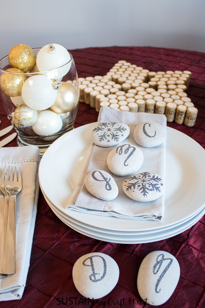 A festive place setting embellished with snowflake and monogram stones as napkin settings. An example of a simple rock crafts ideas using the Cricut Maker.