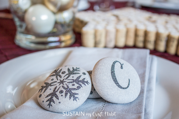 Beach stones embellished with delicate black glitter snowflakes and the letter C displayed on a napkin