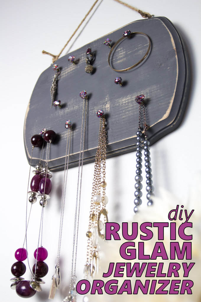 Wooden jewelry organizer hanging on a wall adorned with necklaces