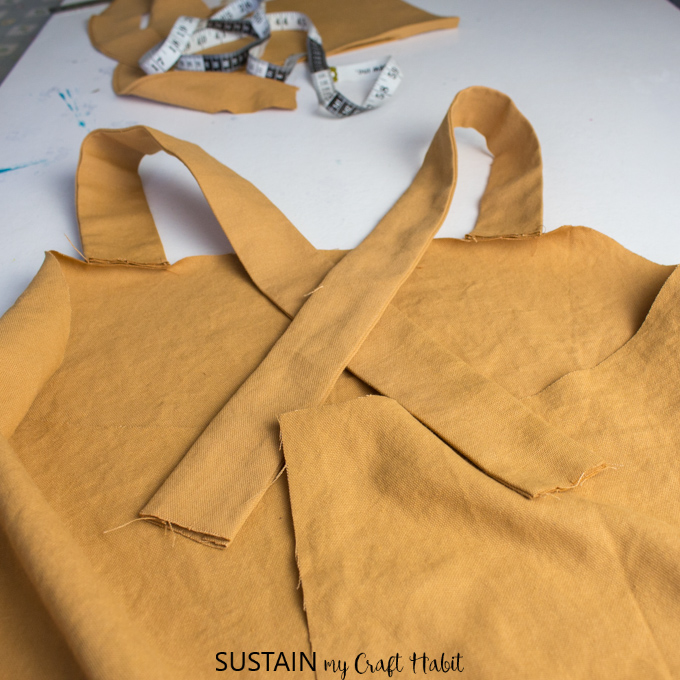Arranging the shoulder straps to criss-cross at the back of the utility apron pattern