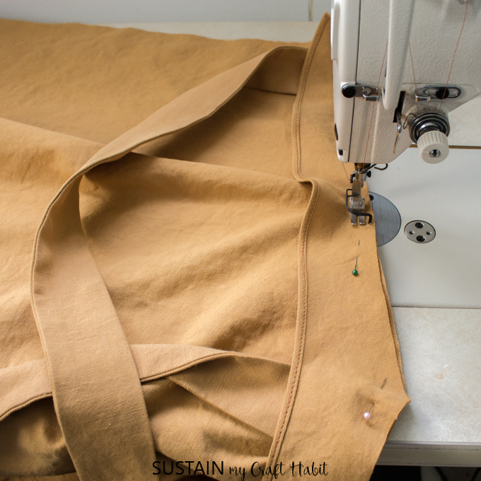 Stitching the shoulder straps in place for a DIY apron pattern