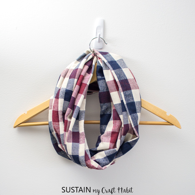 An handmade plaid infinity scarf wrapped around a wooden hanger, hanging on the wall