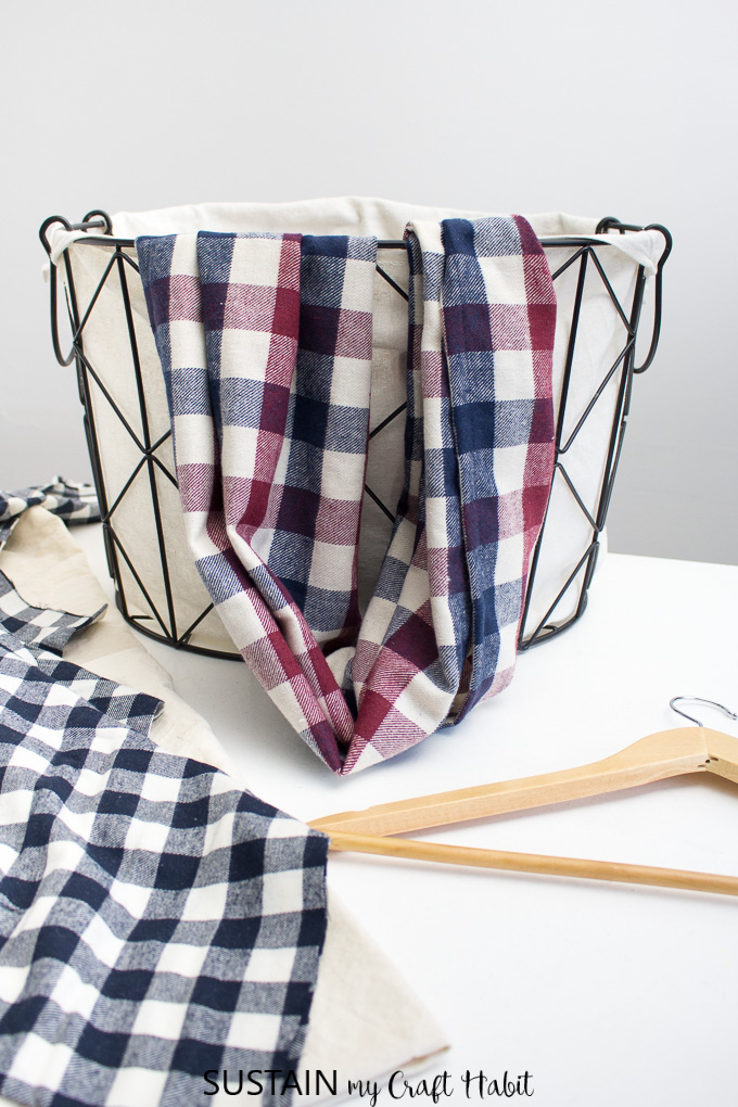 Beautiful handmade burgundy and blue plaid infinity scarf draped over a farmhouse style basket as an example for this how to sew an infinity scarf tutorial