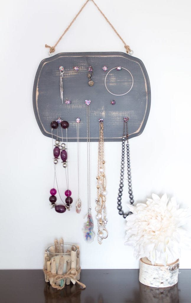 A rustic jewelry organizer hung on the wall.