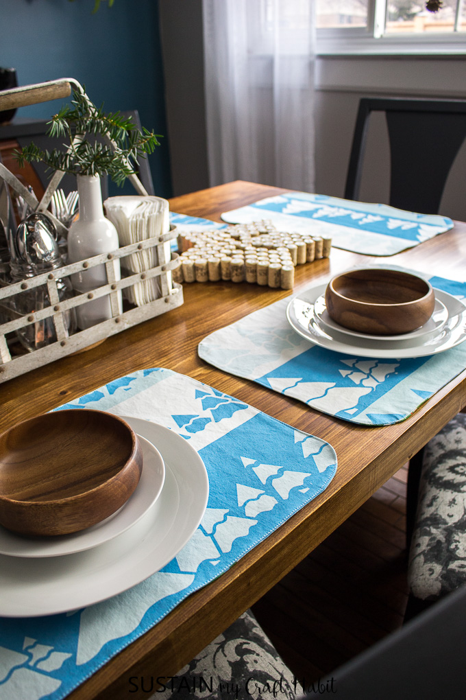 Beautiful wooden table set with handmade placemats in a rustic, winter theme