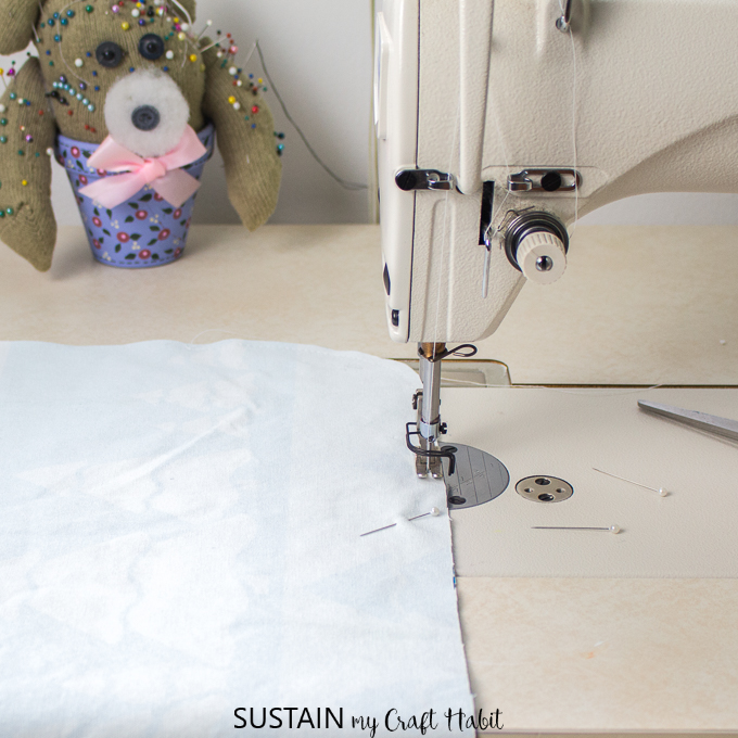 Stitching together two printed fabrics with a sewing machine to make placemats.