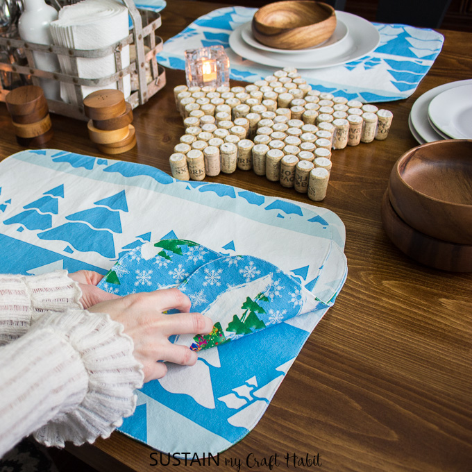 Handmade reversible placemats with winter and Christmas themes on a rustic wood table top