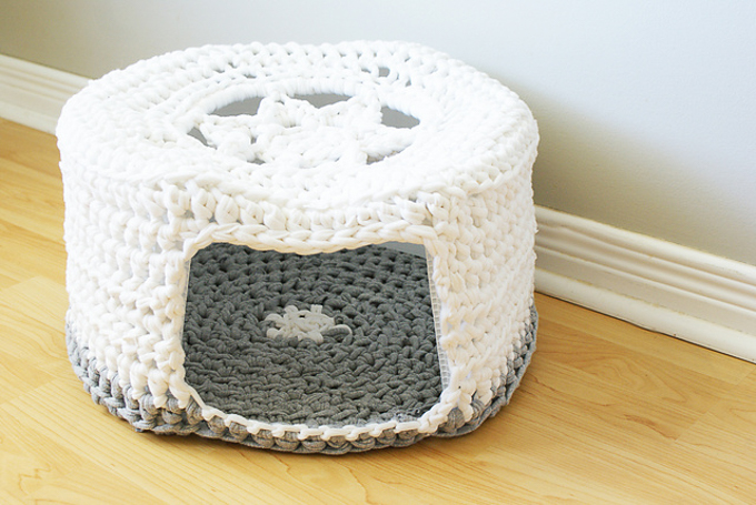 A DIY crochet pet bed made with upcycled white and gray t-shirt yarn