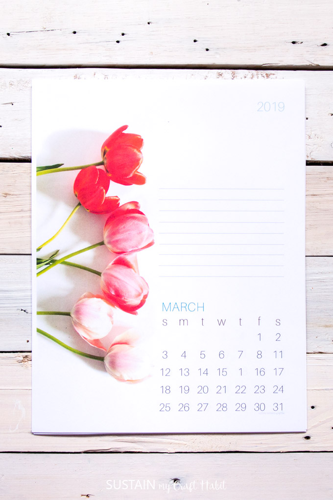 Photo of an printed March calendar page with tulips on a rustic wood backdround