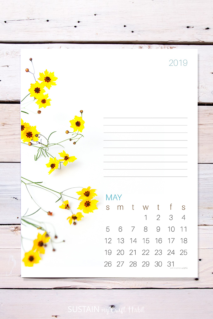 Photo of a printed May calendar page on a rustic wood background