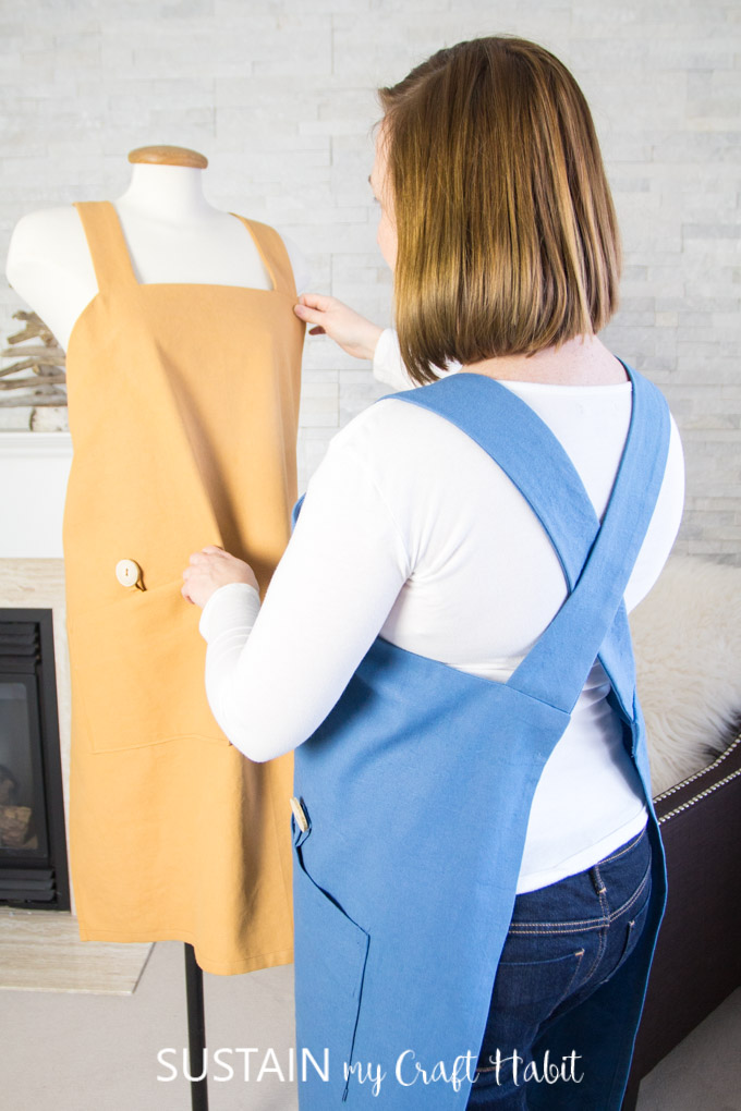 Woman wearing a blue cotton utility apron hanging a mustard colored one made from a DIY apron pattern