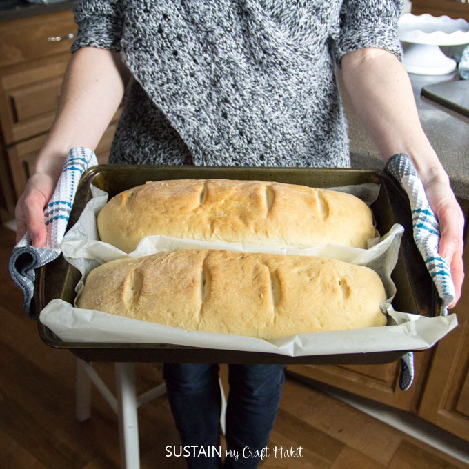 Woman holding two fresh baked loaves of white bread on a baking sheet made from this easy bread recipe