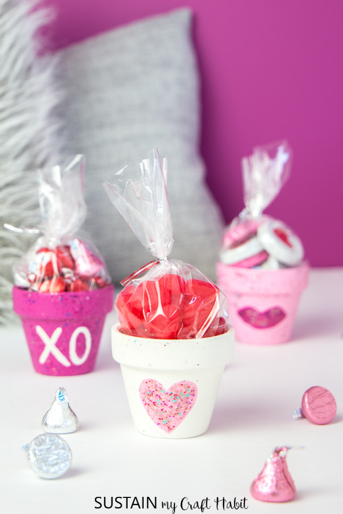Mini clay pots painted in pinks and whites, filled with sweet treat for Valentine's Day