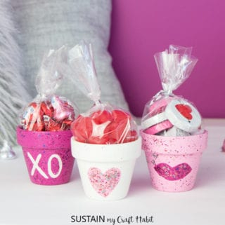 Pink and white painted clay pots filled with sweet treats for Valentine's Day