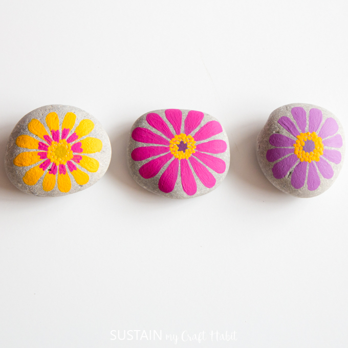 Yellow, pink and purple painted flower rocks side by side on a white background.