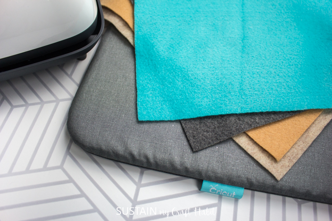 Teal, gray and mustard colored felt fabric on top of a Cricut heat press mat.