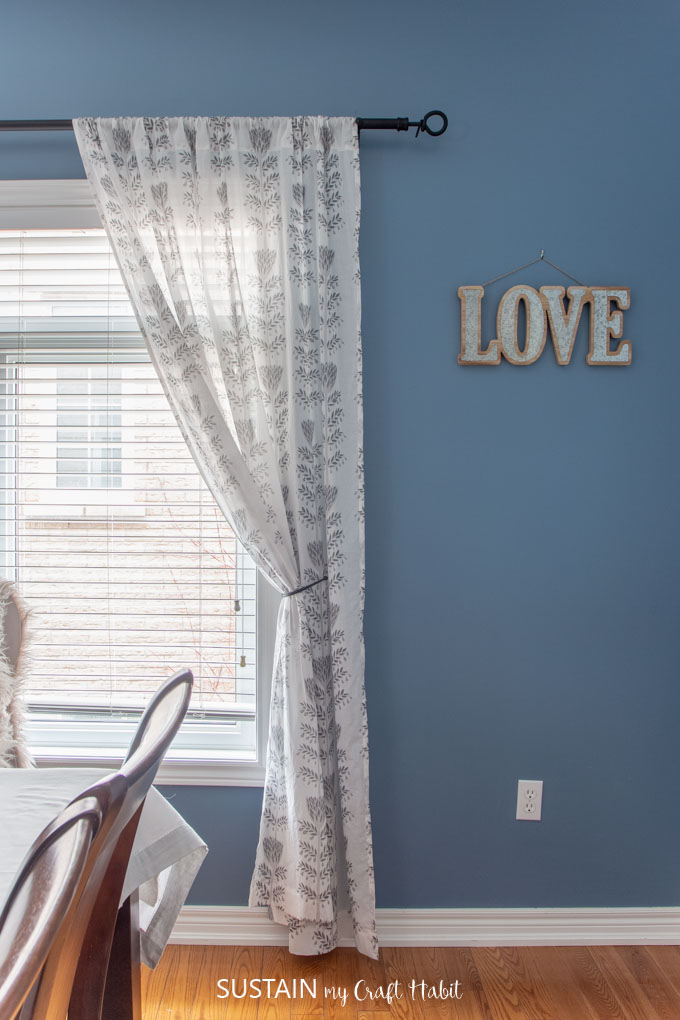One handmade curtain panel hanging from a black curtain rod in a dining room painted with blue walls