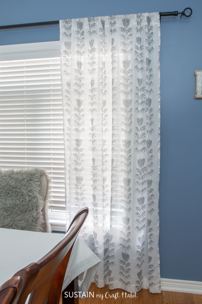 Handmade sheer pocket curtains hanging from a black rod across a dining room window