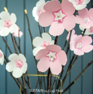 Pink and white paper cherry blossoms glued onto twigs against a teal blue wall