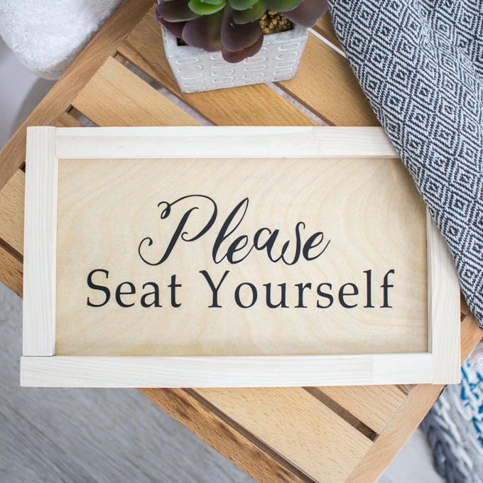"A handmade wood sign on a wooden bench in a bathroom. The phrase ""Please seat yourself"" is written on the sign."