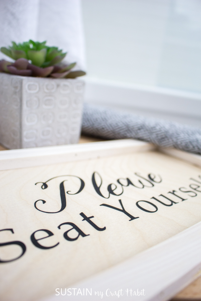 "A small wood sign saying ""Please Seat Yourself"" as an example of how to use the Cricut EasyPress on wood."