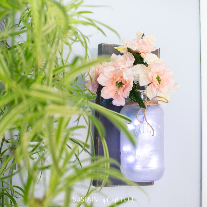 A frosted Mason Jar hanging from a wooden backing, filled with pink flowers and twinkle lights.