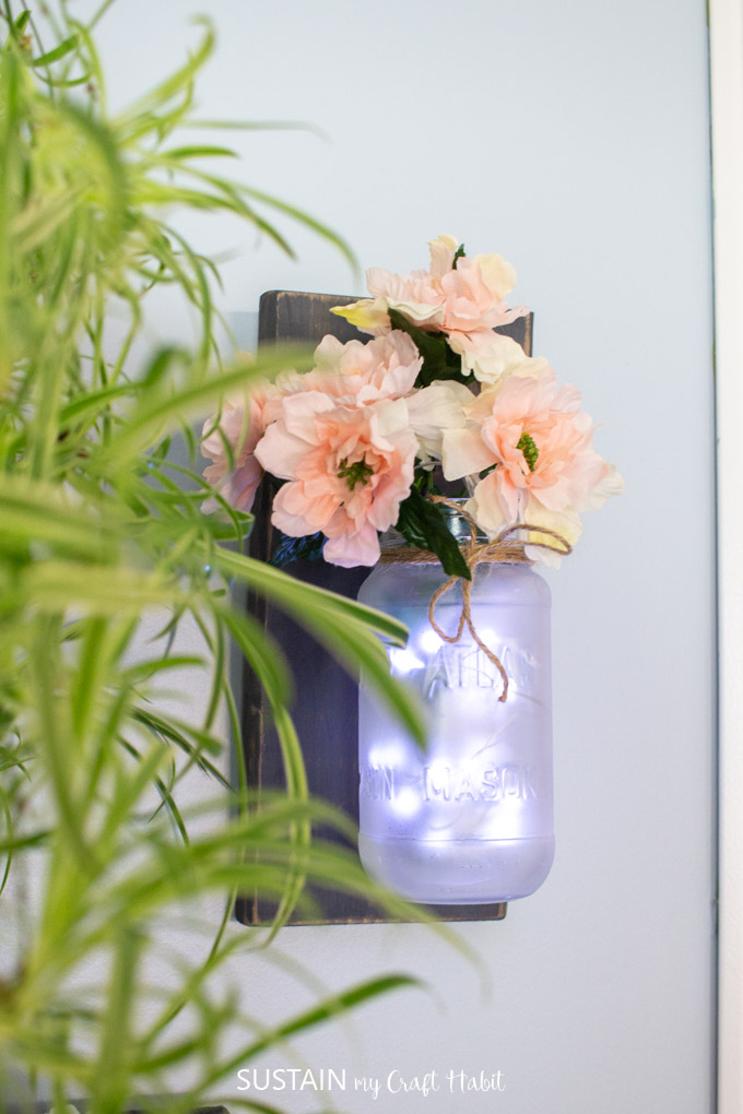 mason jar lantern displayed on a wall.