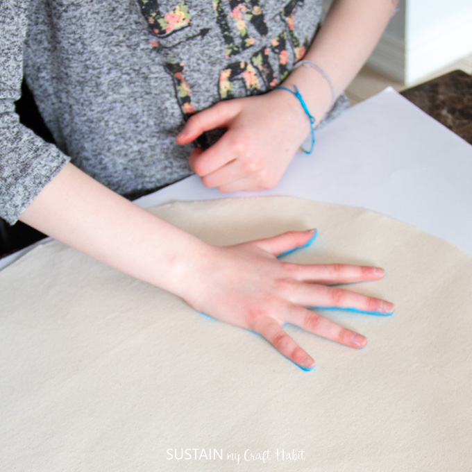 Child pressing their painted hand down onto canvas fabric