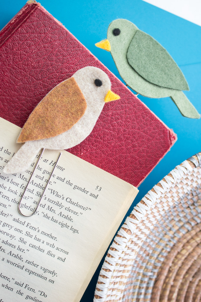 Two felt bird bookmarks place into a red leather book against a bright blue background.