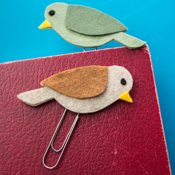 A brown felt bird bookmark lying on the surface of a red leather book cover. A second green felt bird bookmark is peaking out of the top of the book.
