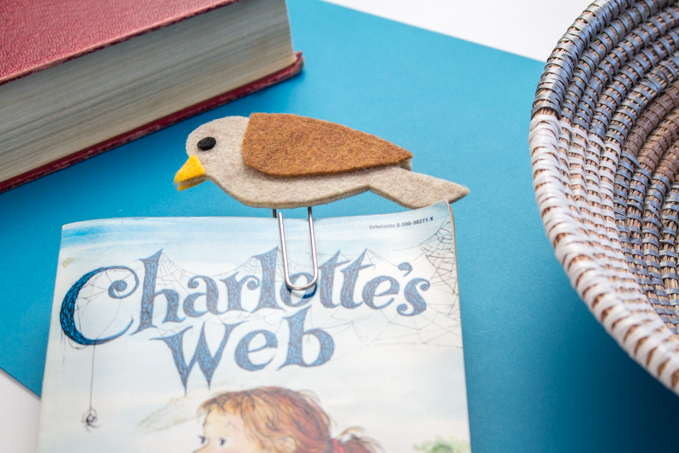 A completed brown felt bird bookmark placed in the cover of the book Charlotte's Web.