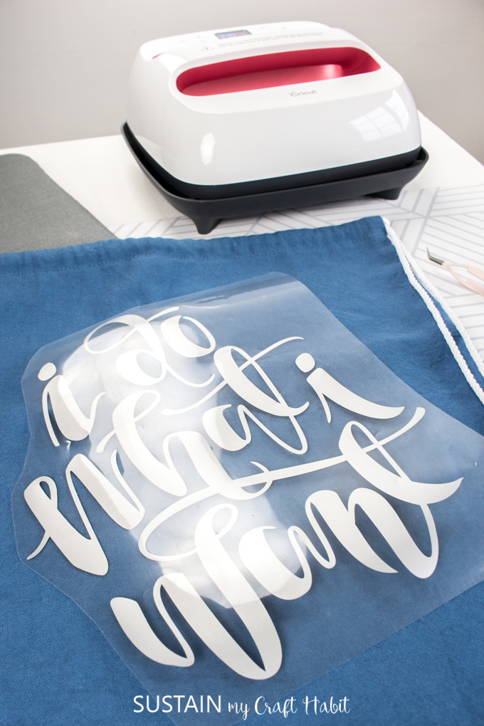 Positioning iron-on vinyl onto the blue canvas drawstring tote bag.