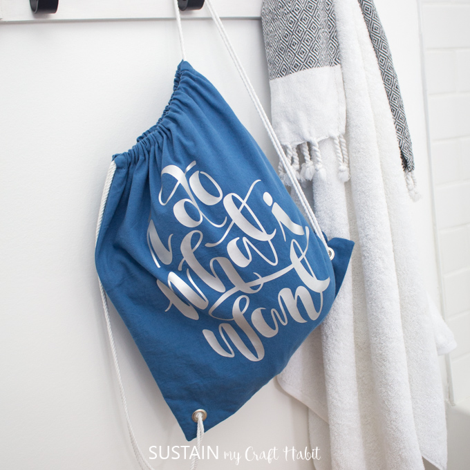 A DIY drawstring bag, with vinyl lettering, hanging from a hook against a white wall.