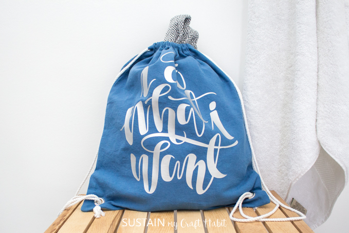 "A drawstring cinch bag, made from blue canvas fabric and white drawstring cord with the phrase ""I do what I want"" pressed onto it with silver vinyl."