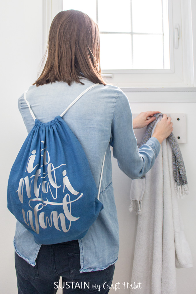 "Woman hanging a towel onto a rack, wearing a drawstring tote bag with the phrase ""I do what I want""."
