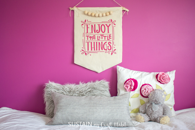A DIY canvas wall hanging from canvas fabric and driftwood on a magenta pink wall