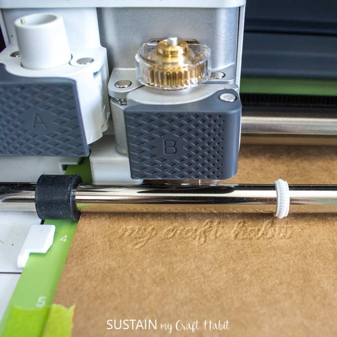 Close up image of the Cricut Maker in action, debossing a piece of light chip board.
