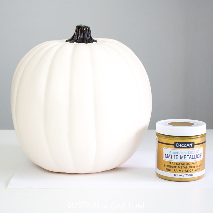 One white pumpkin and one jar of DecoArt matte metallics paint in gold color.